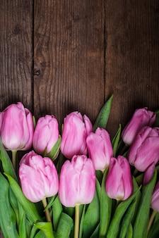 Tulipes roses sur une vieille table en bois en arrière-plan