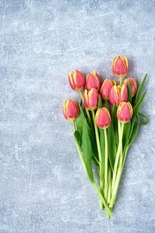 Tulipes rouges sur béton gris.