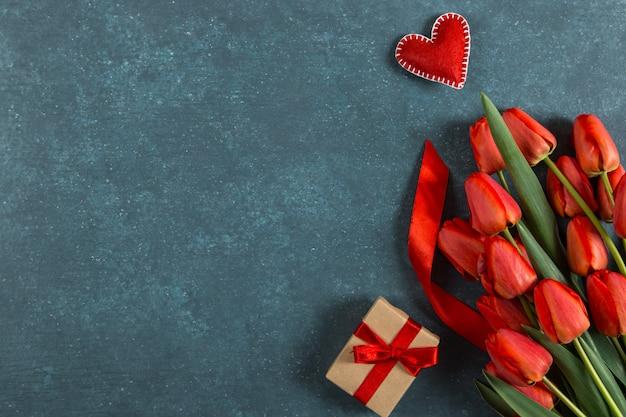 Tulipes rouges, coeur et cadeau sur bleu, carte postale vierge, vacances de printemps, fête des mères. copiez l'espace.
