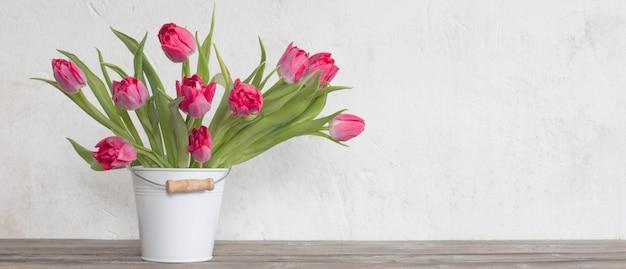 Tulipes rouges dans un seau sur le vieux mur blanc