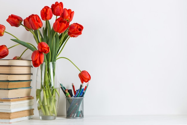 Tulipes rouges dans un vase, livres et fournitures scolaires sur blanc.
