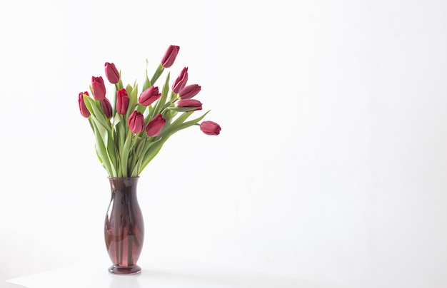 Tulipes rouges dans un vase en verre sur une surface blanche