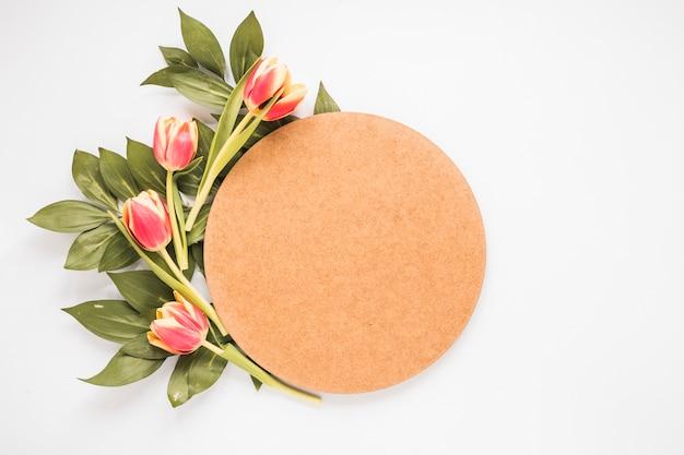 Tulipes rouges avec du papier vierge sur la table