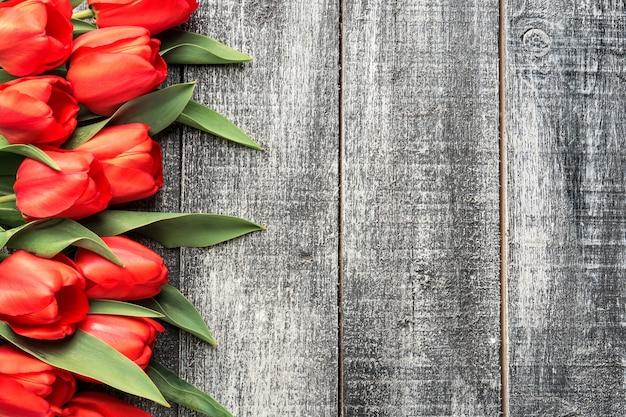 Tulipes rouges sur fond de bois noir et blanc, vue de dessus plat