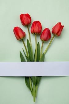 Tulipes rouges sur fond vert avec une bande de papier blanc. concept minimal de célébrations printanières créatives.