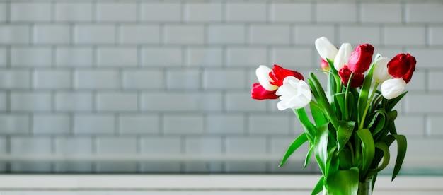Tulipes rouges fraîches dans la cuisine. présent de mari, mec.