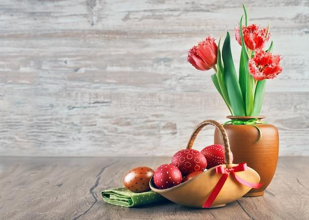 Tulipes rouges et oeufs de pâques peints sur bois, espace de texte