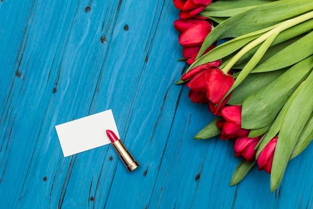 Tulipes rouges sur une planche de bois bleue