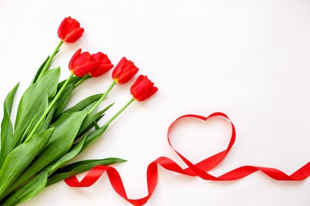 Tulipes rouges et un ruban coeur. saint valentin, fête des mères, mariage, concept de journée des femmes