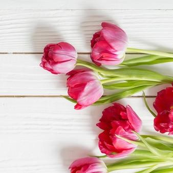 Tulipes rouges sur une surface en bois blanche