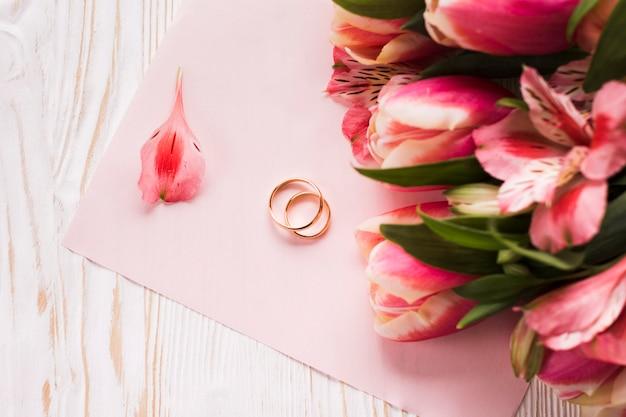 Tulipes sur table à côté des bagues de fiançailles