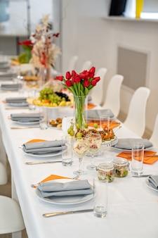 Tulipes sur table de fête table de service avec apéritifs canapés salades en bocaux