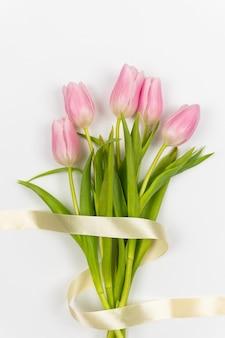 Tulipes tendrement roses avec ruban sur fond blanc saint valentin pâques fête des mères s