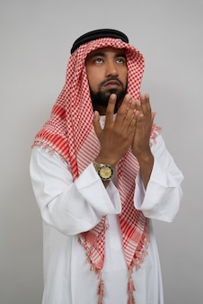 Un turban musulman arabe prie avec les deux mains levées