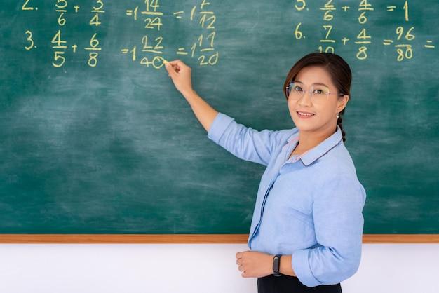 Tuteur enseignant primaire asiatique expliquant les mathématiques dans le tableau noir donnant des cours à distance en ligne