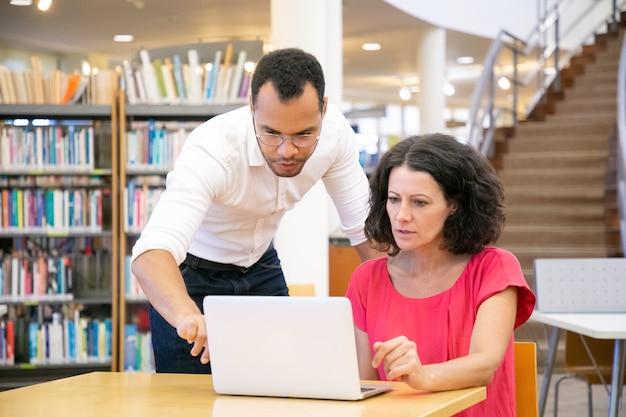 Tuteur expliquant la recherche spécifique à l'étudiant en bibliothèque