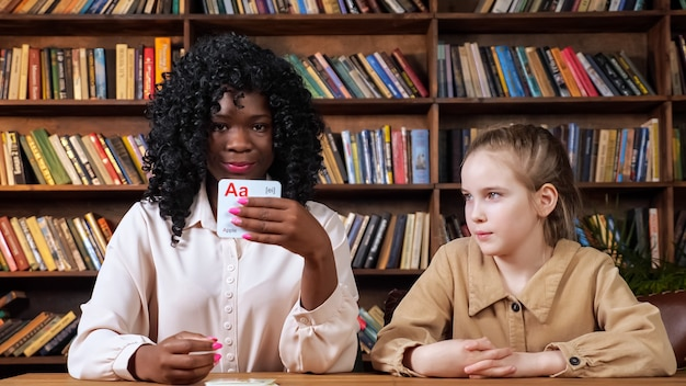 Un tuteur noir individuel enseigne des lettres d'écolière blonde avec des cartes mémoire spéciales assises à table contre des étagères avec des livres à l'isolement covid