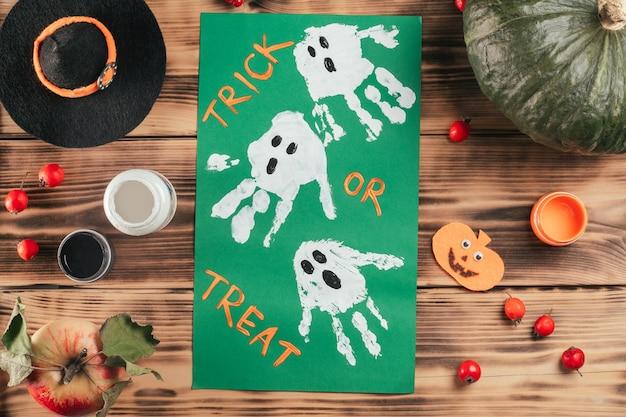 Tutoriel halloween étape par étape, empreinte de la main de l'enfant fantôme. étape 10 : ajoutez trick or treat, ou ce que vous voulez. vue de dessus