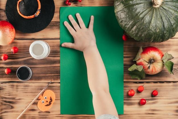 Tutoriel halloween étape par étape, empreinte de la main de l'enfant fantôme. étape 4: l'enfant laisse une empreinte de palmier sur un morceau de papier de couleur. vue de dessus