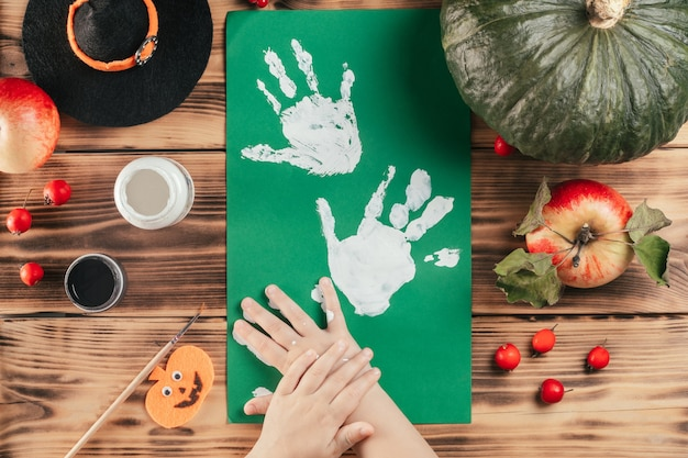 Tutoriel halloween étape par étape, empreinte de la main de l'enfant fantôme. étape 6 : l'enfant laisse une empreinte de palmier sur un morceau de papier de couleur. vue de dessus