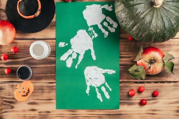 Tutoriel halloween étape par étape, empreinte de la main de l'enfant fantôme. étape 7 : retournez une feuille de papier avec des empreintes de palmiers blancs. vue de dessus