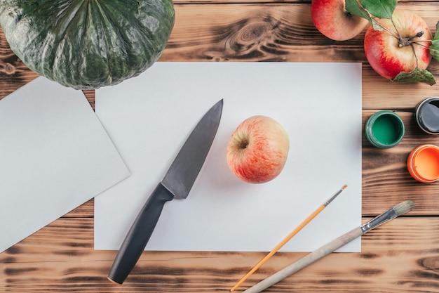 Tutoriel d'halloween étape par étape pour enfants, empreintes de pommes citrouilles. étape 1 : vous aurez besoin d'une feuille de papier blanc, d'une pomme, d'un couteau, de gouache orange, verte et noire ou de peintures acryliques et d'un pinceau. vue de dessus