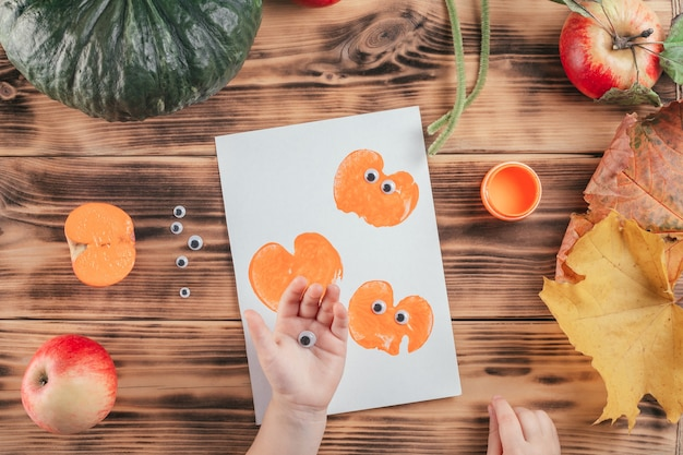 Tutoriel d'halloween étape par étape pour enfants, empreintes de pommes citrouilles. étape 11: la main de l'enfant tient les yeux pour coller l'impression de citrouille. vue de dessus