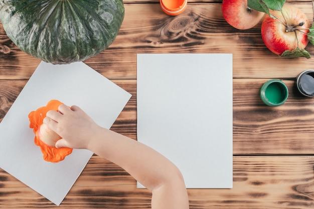 Tutoriel d'halloween étape par étape pour enfants, empreintes de pommes citrouilles. étape 6 : la main de l'enfant trempe la moitié de la pomme dans de la gouache orange sur du papier. vue de dessus