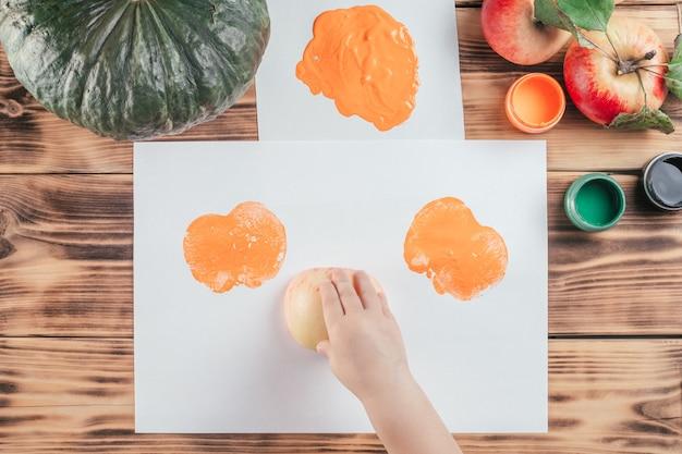 Tutoriel d'halloween étape par étape pour enfants, empreintes de pommes citrouilles. étape 8 : la main de l'enfant laisse des empreintes sur papier avec la moitié de la pomme peinte à la gouache orange. vue de dessus