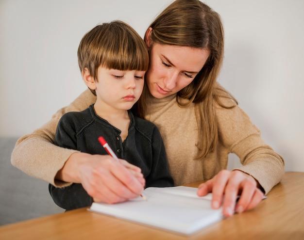 Tutrice aidant l'enfant à écrire à la maison