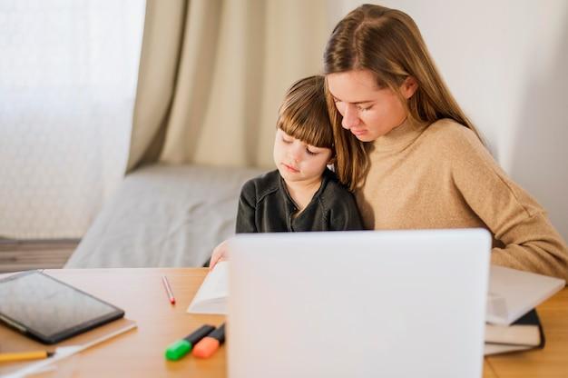 Tutrice enseignant l'enfant à la maison avec un ordinateur portable