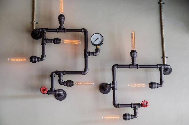 Tuyau en acier et lampe sur le mur