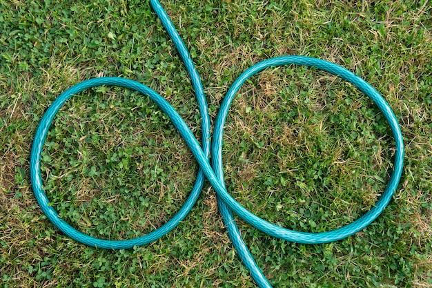 Tuyau d'arrosage allongé sur l'herbe verte sous la forme d'un signe de l'infini