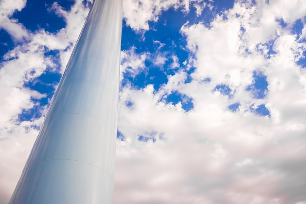 Tuyau blanc métallique épais en position verticale comme base d'une tour, isolé sur fond de ciel bleu.
