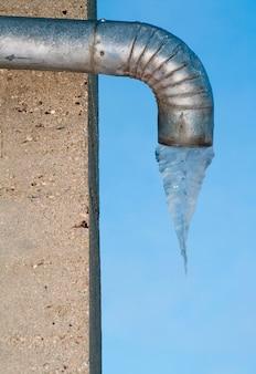 Tuyau de drainage en métal avec de l'eau gelée en dessous