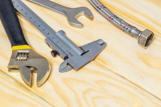 Tuyau d'eau et set d'outils pour plombiers sur des planches en bois préparés avant le travail