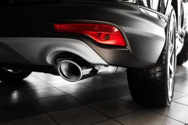 Tuyau d'échappement de voiture. pot d'échappement d'une voiture de luxe. détails de l'intérieur de la voiture élégante, intérieur en cuir. fermer