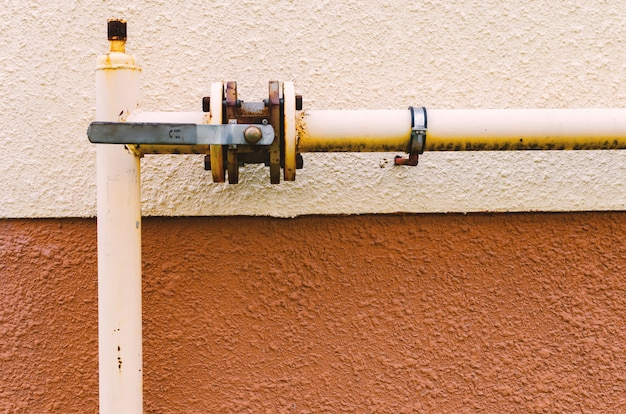 Un tuyau de gaz jaune avec une grue longe la façade d'un nouveau bâtiment à plusieurs étages.