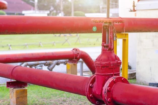 Tuyau d'incendie en fer rouge et grande vanne pour l'eau s'alignent dans une longue rangée