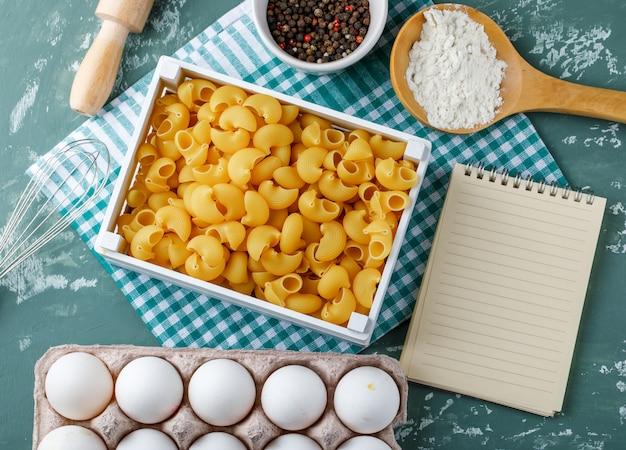 Tuyau de pâtes rigate dans une boîte avec des œufs, des grains de poivre, de l'amidon, un rouleau à pâtisserie, un fouet et un cahier