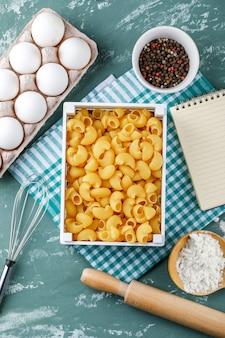 Tuyau de pâtes rigate avec des œufs, des grains de poivre, de l'amidon, un fouet, un rouleau à pâtisserie et un cahier sur un torchon