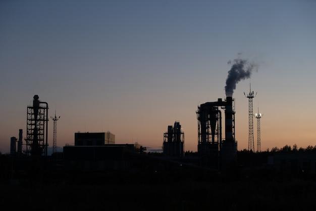 Tuyau d'usine air polluant contre le coucher du soleil
