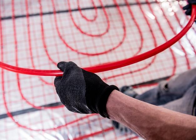 Le tuyauteur installe le système de chauffage par le sol à la maison