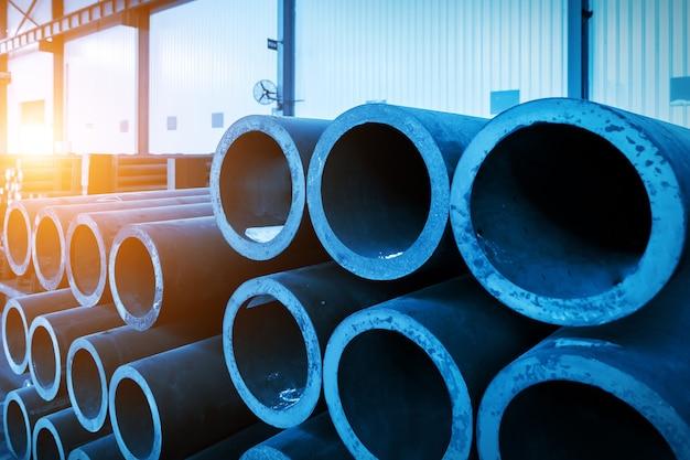 Les tuyaux en acier sont empilés dans l'entrepôt de l'atelier