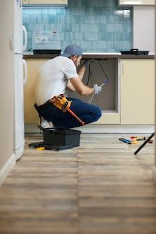 Les tuyaux doivent être entretenus jeune plombier professionnel réparateur portant une ceinture à outils accroupie sur le