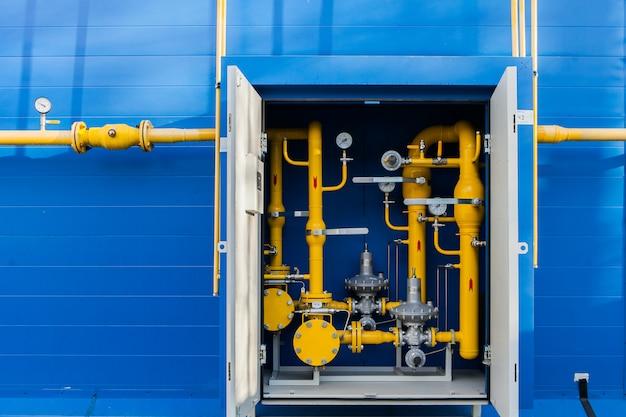Tuyaux à gaz sur le mur de la buanderie recouverts de panneaux de revêtement bleu. vanne de gazoduc jaune dans une boîte à outils en métal de communication arrière de chaudière.