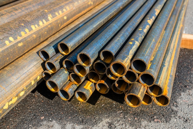 Tuyaux métalliques ronds sur asphalte, gros plan