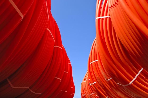 Des tuyaux en plastique empilés en rouleaux dans la rue