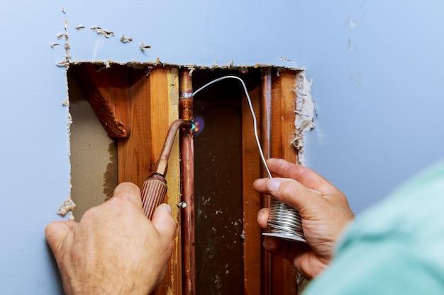 Tuyaux et raccords en métal du système d'alimentation en eau domestique vus à travers un trou dans un mur blanc