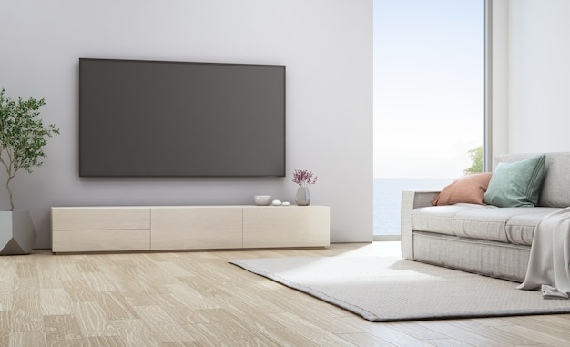 Tv sur un mur blanc près d'un canapé dans une maison de vacances ou une villa de vacances. intérieur de l'hôtel 3d illustrati